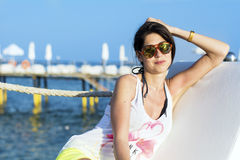 Happy woman enjoying the summer vacation laying on sunbed on the beach Royalty Free Stock Photo