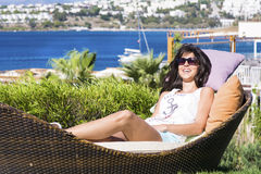 Happy woman enjoying the summer vacation laying on sunbed in a tropical garden Stock Photos