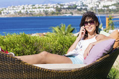Happy woman enjoying the summer vacation laying on sunbed in a tropical garden Royalty Free Stock Photography