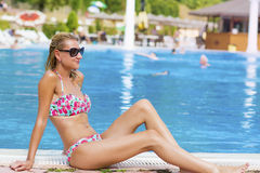 Happy woman enjoying the summer vacation laying on sunbed in a tropical garden Royalty Free Stock Images