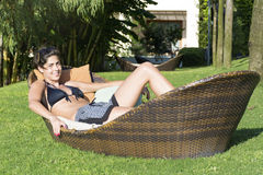 Happy woman enjoying the summer vacation lying on sunbed in a tropical garden Stock Photography