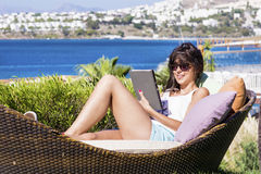 Happy woman enjoying the summer vacation with tablet in the hands Stock Image