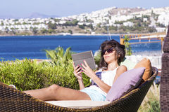 Happy woman enjoying the summer vacation with tablet in the hands Royalty Free Stock Photos