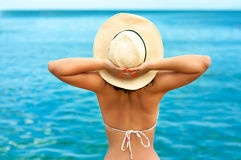 Happy woman enjoying the sun on seaside beach with hat Royalty Free Stock Photography