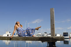 Happy Woman enjoying sunny day at Marina. An attractive looking woman in a long blue summer dress is sitting on a wooden boardwalk over the tranquil water of a Stock Photo