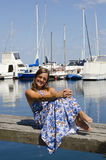 Happy Woman enjoying sunny day at Marina. An attractive looking woman in a long blue summer dress is sitting on a wooden boardwalk over the tranquil water of a Royalty Free Stock Image