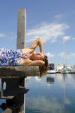 Happy Woman enjoying sunny day at Marina. An attractive looking woman in a long blue summer dress is sitting on a wooden boardwalk over the tranquil water of a Stock Image