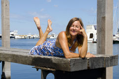Happy Woman enjoying sunny day at Marina. An attractive looking woman in a long blue summer dress is sitting on a wooden boardwalk over the tranquil water of a Royalty Free Stock Photos