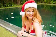 Happy woman enjoying winter holidays in the pool. With santa hat Royalty Free Stock Images