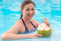 Happy woman enjoys delicious coconut milk while. In the pool Stock Images