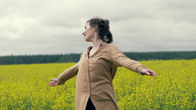 Happy woman enjoys a summer walk in field. Summer field yellow flowers. Happy woman enjoys a summer walk in field slow motion. Close up beautiful young woman stock footage