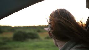 Happy woman enjoys traveling by car in summertime. Hand in the air through the window of a car. Sunset rays. Slow mo. Happy pretty woman enjoys traveling by car stock video footage