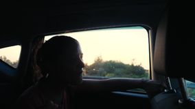 Happy young woman enjoys traveling by car in summer time. Sunset rays. Slow motion, sings song and dances. 1920x1080. Happy woman enjoys traveling by car in stock footage