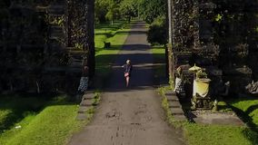 Happy woman entering Balinese traditional gate stock footage