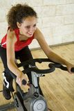 Happy woman on exercise bike Stock Image