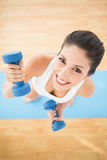 Happy woman exercising with dumbbells on blue exercise mat smili Royalty Free Stock Image