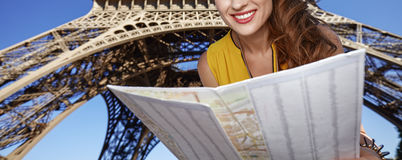 Happy woman exploring attractions in front of Eiffel tower Royalty Free Stock Images