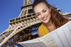 Happy woman exploring attractions in front of Eiffel tower Stock Photos