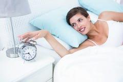 Happy woman extending hand to alarm clock Stock Photo