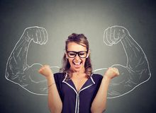 Happy woman exults pumping fists celebrates success. On gray wall background Royalty Free Stock Photos