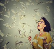 Happy woman exults pumping fists ecstatic celebrates success under a money rain Royalty Free Stock Image