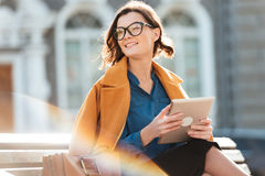 Happy woman in eyeglasses holding tablet computer and looking away. Happy young woman in eyeglasses holding tablet computer and looking away while sitting on a Royalty Free Stock Photos