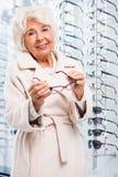 Happy woman at eyeglasses store stock image