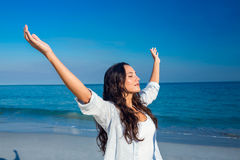 Happy woman with eyes closed at the beach. On a sunny day stock photo