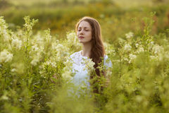 Happy woman with eyes closed among the wildflowers Royalty Free Stock Photo