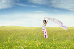 Happy woman with fabric in the meadow Stock Image
