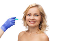 Happy woman face and beautician hand with syringe Royalty Free Stock Photography