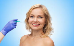 Happy woman face and beautician hand with syringe Royalty Free Stock Image