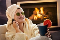 Happy woman in facial pack on phone Royalty Free Stock Image