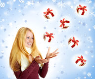 Happy woman with falling christmas gift Royalty Free Stock Photos