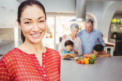 Happy woman with family preparing food in background Stock Photos
