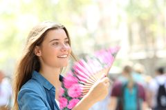 Happy woman fanning in the street royalty free stock image