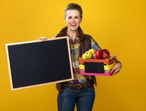 Happy woman farmer with box of apples showing blank board Royalty Free Stock Image