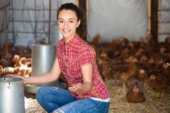 Happy woman farmer giving feeding stuff Royalty Free Stock Photo