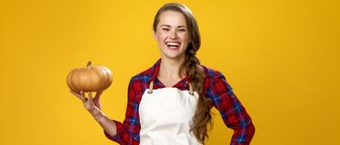 Happy woman farmer isolated on yellow background with pumpkin Royalty Free Stock Photos