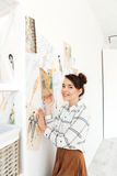 Happy woman fashion illustrator drawing. Image of young happy woman fashion illustrator standing near a lot of illustrations and drawing. Looking at camera Stock Images