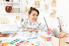 Happy woman fashion illustrator sitting at the table. Photo of young happy woman fashion illustrator sitting at the table and drawing. Looking at camera Stock Image