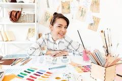 Happy woman fashion illustrator sitting at the table. Photo of young happy woman fashion illustrator sitting at the table and drawing. Looking at camera stock image
