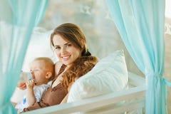 Happy woman feeding baby Stock Photos