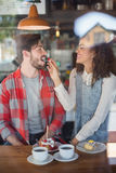 Happy woman feeding cherry to male friend Royalty Free Stock Images