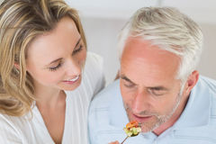 Happy woman feeding her partner a spoon of vegetables Royalty Free Stock Photo