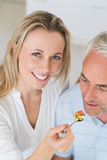 Happy woman feeding her partner a spoon of vegetables Royalty Free Stock Image