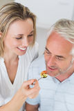Happy woman feeding her partner a spoon of vegetables Royalty Free Stock Photos
