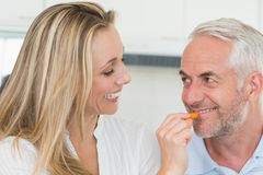 Happy woman feeding her partner vegetable piece Royalty Free Stock Images