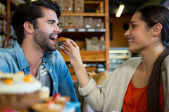 Happy woman feeding man with dessert Royalty Free Stock Image