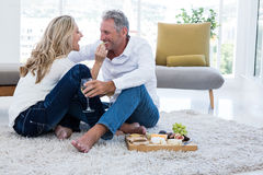 Happy woman feeding man at home Stock Image